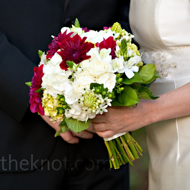 Red dahlias and green hydrangeas popped against the bride's simple dress.