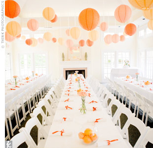 The reception tables were set up family-style to encourage guests to relax and enjoy themselves. Orange centerpieces, napkin ties, and lanterns tied in the signature color.