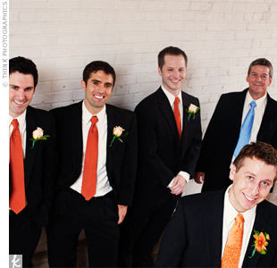 The groomsmen wore classic black suits paired with bright orange ties, and the groom's dad wore a silver tie. The groom wore a light orange tie to stand out.