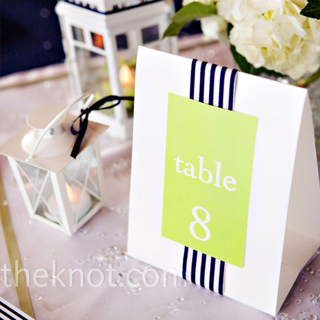 White handkerchiefs with lime green borders were placed at the center of each table to highlight the white hydrangea centerpieces, the table numbers, and the lanterns of various sizes.