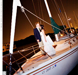 "Instead of leaving the wedding by car, Amanda and Ben rented a sailboat! They slipped away from the dance floor for a few photos, then when the DJ played ""Somewhere Across the Sea,"" guests headed out to the deck to cheer and wave goodbye."