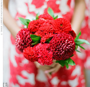 To complement their red and ivory floral print dresses, the bridesmaids carried dahlias and a mix of other red accent flowers.
