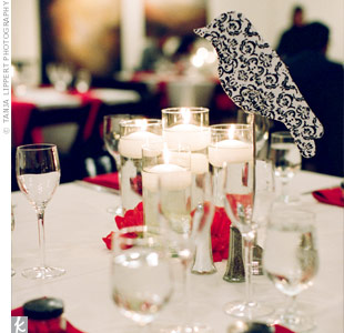 The pattern of the escort bags corresponded with a homemade stuffed bird. Guests had to match the fabrics to figure out which table they'd been assigned to. The birds sat perched above five square vases with floating candles and clusters of red dahlias.