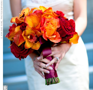 Mimi carried a lush bouquet of fiery peonies, calla lilies, roses and orchids. The stems were loosely wrapped with burgundy-pink satin ribbon.