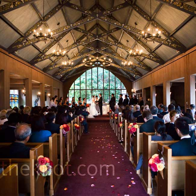 The couple chose a non-denominational chapel with beautiful, painted exposed ceiling beams and floor to ceiling windows behind the altar.