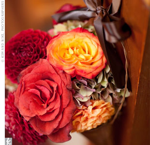 Red, pink, and orange roses and dahlias and green hydrangea, hung from every other pew along the aisle.