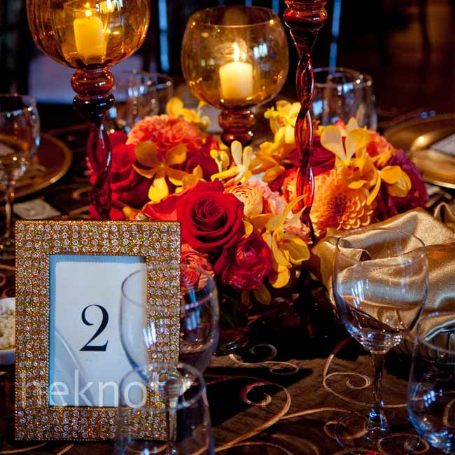 Pretty, glass goblet holders completed the lower centerpieces and obeyed the venue's candle rule that candles must be enclosed at least two inches from the rim of the holder. The gold glitter frames for the table numbers added a bit bling.