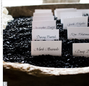 A calligrapher wrote guests' names on thick white stock. The cards were then stood up in a wooden trough filled with black sand and gardenias.