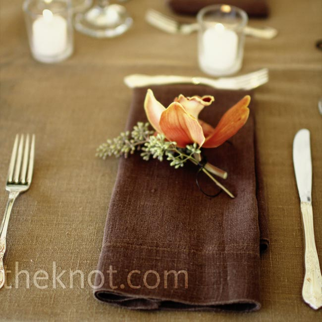 Each place was marked with a chocolate-brown napkin topped with a salmon-colored cymbidium orchid. The orchid motif could be seen in many aspects of the wedding, including the invitations, programs, and boutonnieres.