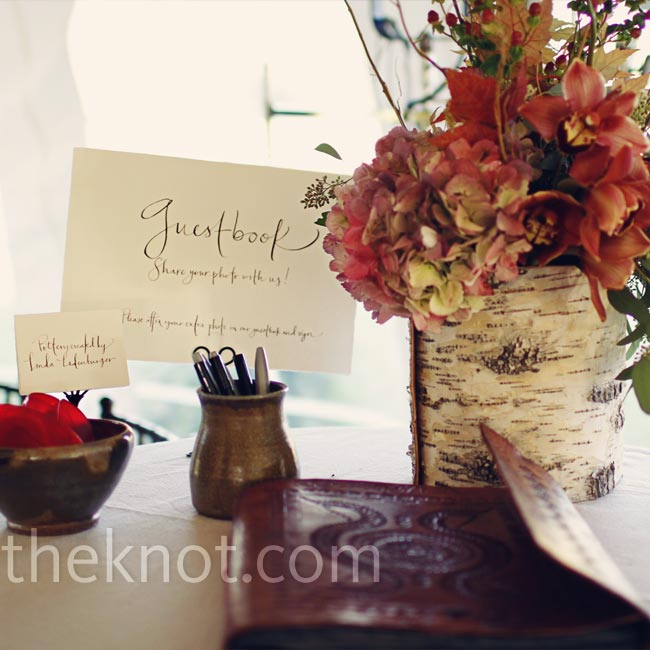 A leather bound book of black handmade paper was set up near a photo booth. Guests were asked to paste in their photos along with a message. Regan decorated the guest book table with a few of her mother's pottery pieces to honor her.