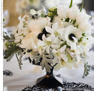 Black footed vases held French anemones, tulips, dendrobium orchids, cymbidium orchids, japhet orchids, and accenting black Billy balls, seasonal foliage, and dusty miller. The arrangements differed slightly on each table but each one reflected the rustic quality of the space.