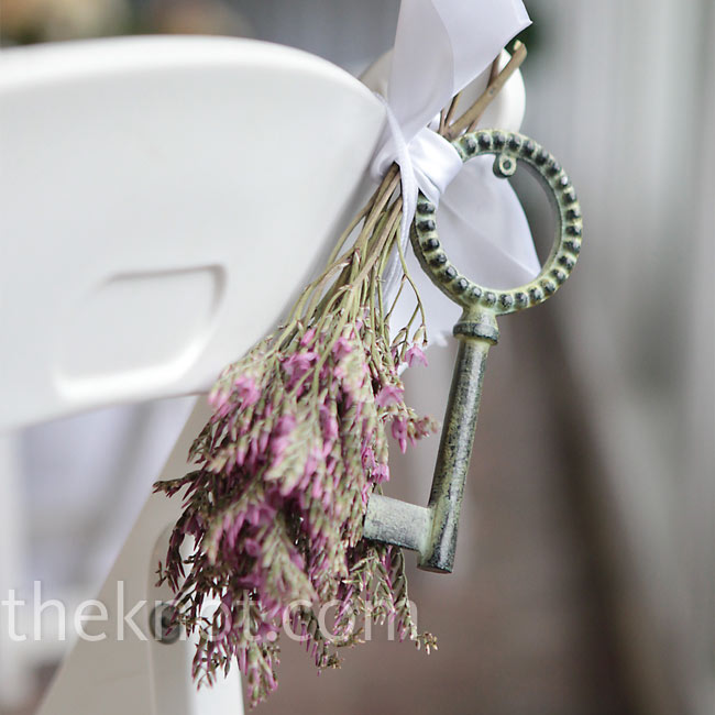 Replicas of vintage keys and dried herbs decorated the ceremony chairs and tied into the rustic theme.