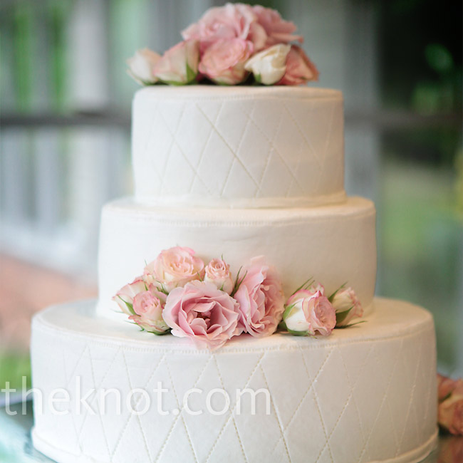 When Brandi couldn't decide exactly what she wanted in her wedding cake, she ended up showing the baker a picture of her gown. The baker then came up with the quilted pattern, which she used on the top and bottom tier of the cake. Leftover flowers from the centerpieces completed the design.