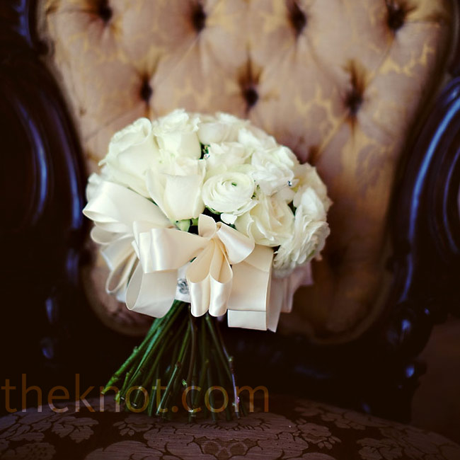 To keep the look elegant, Annah and Travis opted to keep all of the wedding flowers ivory with the exception of their mother's corsages. Annah's florist created a classic ivory bouquet of rose and ranunculus blooms tied with satin ribbon.