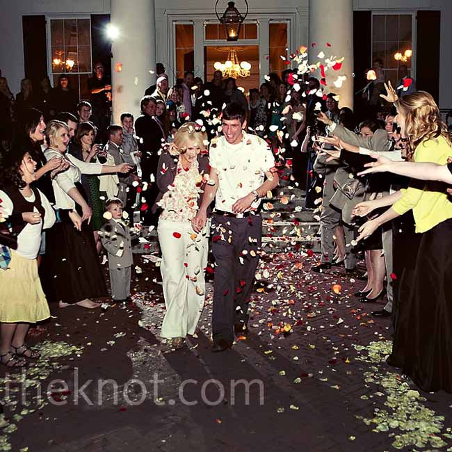 The newlyweds made their ceremony escape amid a shower of rose petals.