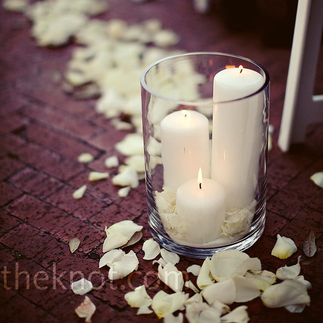 Cylindrical votives holding ivory candles lined the ceremony aisle, and ivory rose petals were sprinkled down the center aisle.