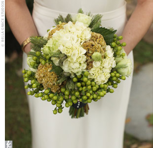 Catherine's organic-style bouquet of green and ivory cockscomb, green hydrangea, lisanthus, wheat, salal leaf, and green hypericum berries was wrapped with a navy ribbon to incorporate the couple's accent color.