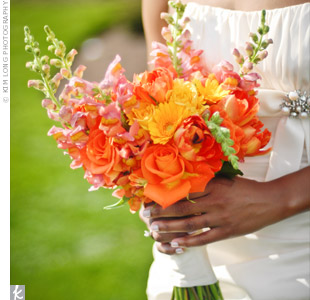 "Alicia describes her bouquet as ""just shy of volleyball size."" It was a blend of orange, gold, and yellow blooms, including roses, tulips, mini gerbera daisies, and snapdragons."