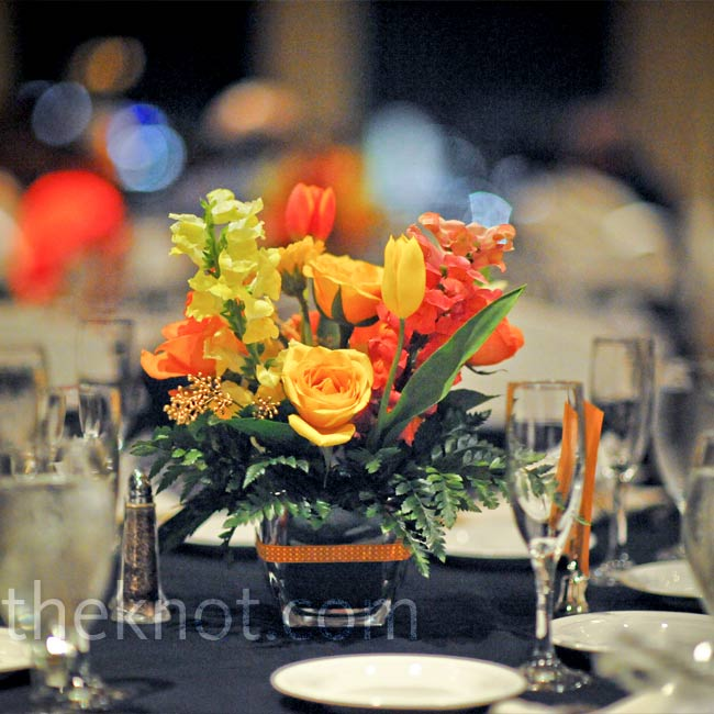 The bright centerpieces were made up of orange and yellow roses, tulips, snapdragons, and gerbera daisies in rounded square vases, which were wrapped with ribbon.