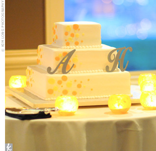 The wedding cake was a modern, three-tiered vanilla confection decorated with orange polka dots and the couple's monogram.