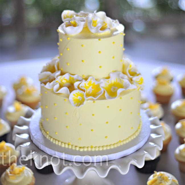 Tara and Mike's two-tiered yellow wedding cake was covered with white and yellow abstract flowers. They also served an assortment of cupcakes in lemon, white chocolate empress, and chocolate devil's food frosted with pale yellow white chocolate truffle icing and yellow-colored chocolate shavings.