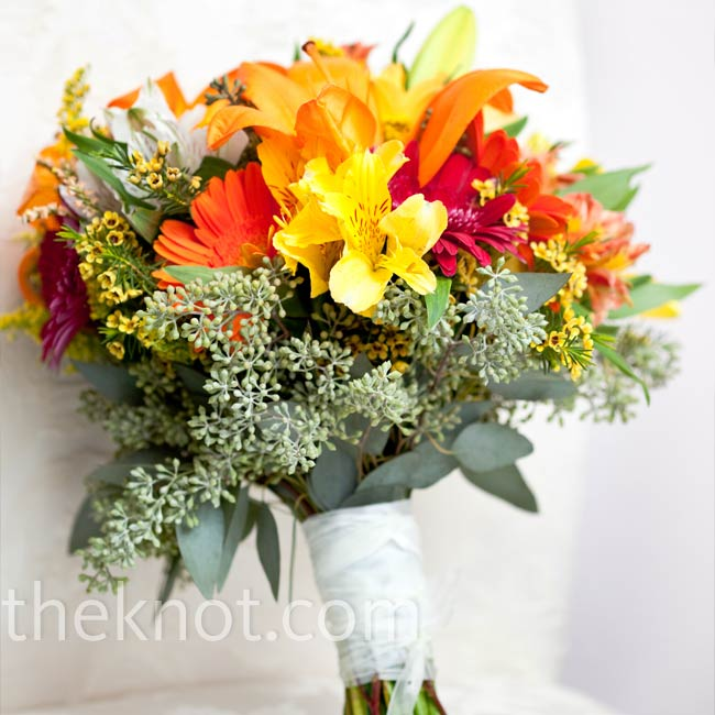 "Shelly told her florist that she wanted a ""wild"" look to her bouquet. The result: a cheerful collection of gerbera daisies, solidago, seeded eucalyptus, alstroemeria, and waxflower."