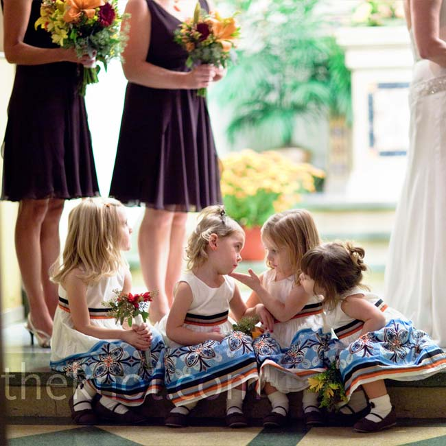 "Shelly had four flower girls (three nieces and one ""pseudo-niece"") in her ceremony. They each wore a high-waisted ivory sleeveless dress with brown, orange and light blue flowers."