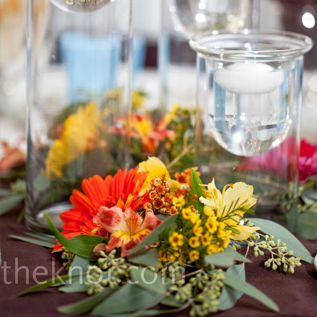To keep the centerpieces simple, Shelly and Paul set up three floating candles in glass pillars of varying heights on each table, and their florist arranged greens and flowers around them.