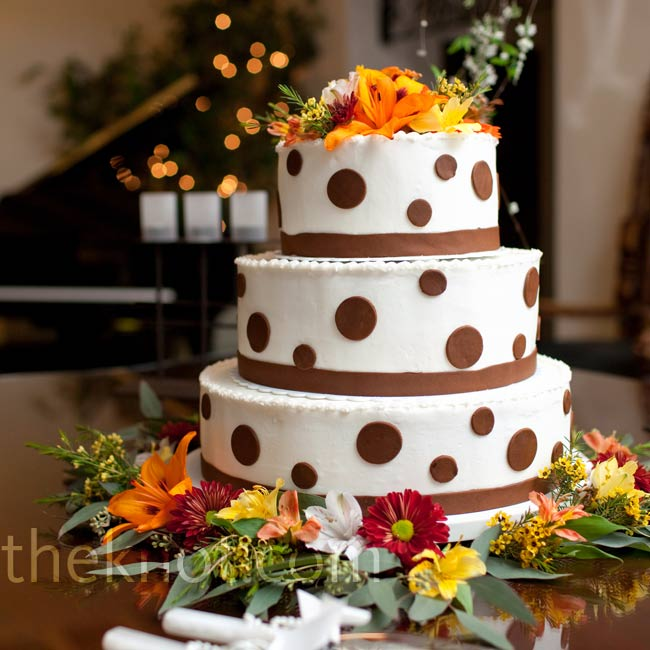 The brown polka dot wedding cake had three different flavors: pina colada with pineapple filling, chocolate raspberry with raspberry filling, and lemon cake with blueberry filling. The top of the cake was decorated with yellow, orange, and red fresh flowers.