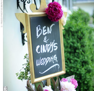Fragrant peonies and roses cradled a chalkboard welcoming guests to Cindy and Bens backyard wedding.