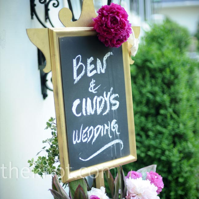 Fragrant peonies and roses cradled a chalkboard welcoming guests to Cindy and Ben's backyard wedding.