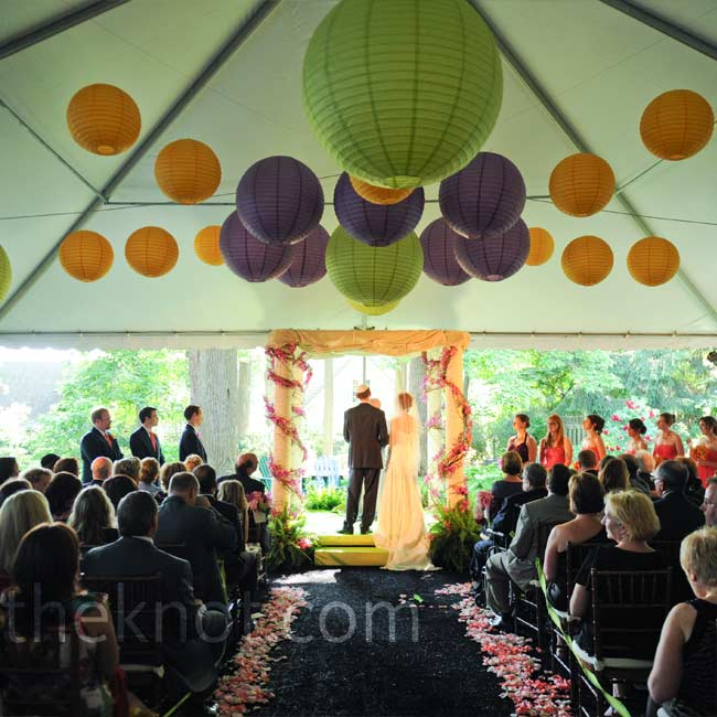 Cindy and Ben stood beneath a flower-trimmed huppah overlooking the backyard. Guests looked on, sheltered by a tent decorated in green, purple, and orange lanterns.