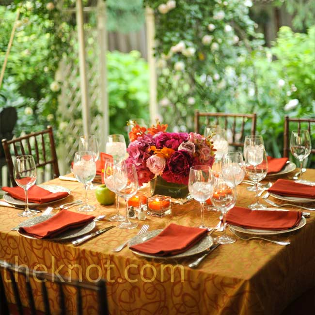 Orange linens with darker orange behind arrangements of full, pink peonies, orchids, and garden roses gave each table a contrasting shot of color.