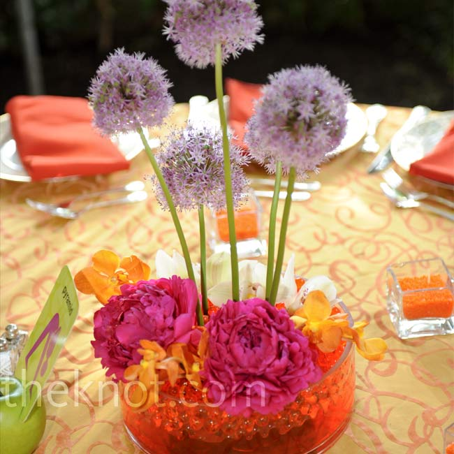 Purple allium hovered above full beds of peonies and roses, giving the centerpieces a contemporary feel. Each design was set in a clear vase filled with shiny orange stones.