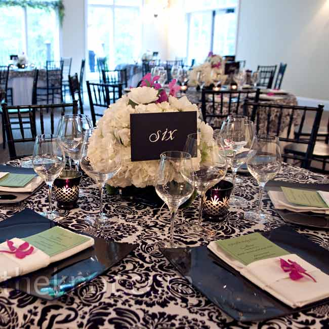The bride and groom introduced a fourth color to their reception style with purple orchids on each place setting. Black square vases held heavy floral arrangements of white hydrangeas, ranunculus, and purple dendrobium orchids looped with bear grass.