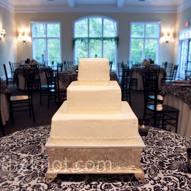 The bride and groom cut into a square, three-tiered cake covered in amaretto-flavored buttercream. A scroll pattern added texture to the top layer and ivory ribbon wrapped around the bottom of each tier.