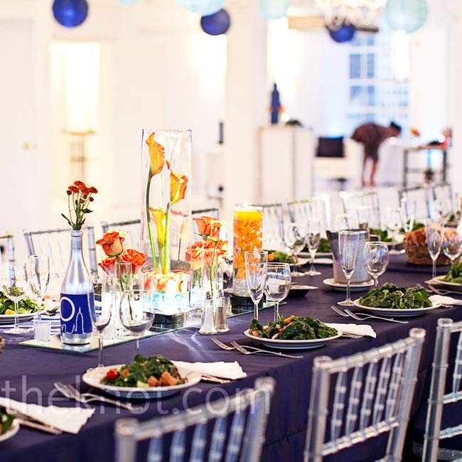 Alicia and Erik chose varying shades of blue and orange as their wedding colors. They gathered boxes and tall round vases, filled each one with flowers and LED lights, and set them atop square mirrors as centerpieces.