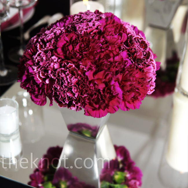 Arrangements of hot pink carnations reflected beautifully off mirrored table runners.