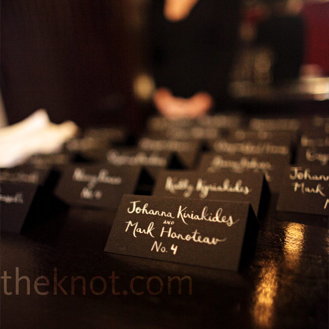 Black tented escort cards with white handwritten names cards kept with the sleek color palette.