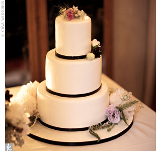 Simple black grosgrain ribbons kept the three-tier fondant cake elegant while sprigs of wild flowers provided a hint of color.