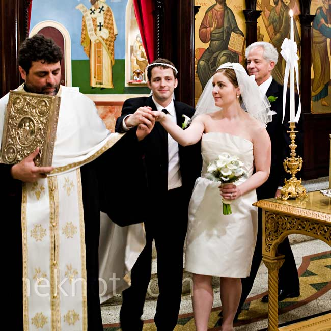 Because John's family is Greek Orthodox, it was important for the couple to have a second, more traditional, ceremony. At this one, Felicia wore a knee-length dress with a blue vintage jacket and a short veil.