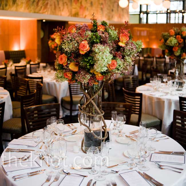 Tall vases filled with hydrangeas, lilies, and roses -- in the shades of purples and orange with pops of green -- added a beautiful height to the space.