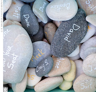 For a nontraditional spin on escort cards, the couple gathered smooth stones from the beach and wrote the guest's first name on one side and the table name on the other.