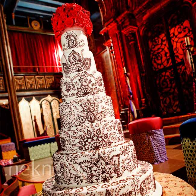 Peri and Marcus wanted the cake to look like Henna designs and match their stationary. The striking combination of dark brown detailing on rolled white fondant was complimented with red sugar roses on top.