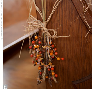 Dried grass, wheat, and fall-colored berries were tied with natural colored raffia and twine and hung from the end of each pew.