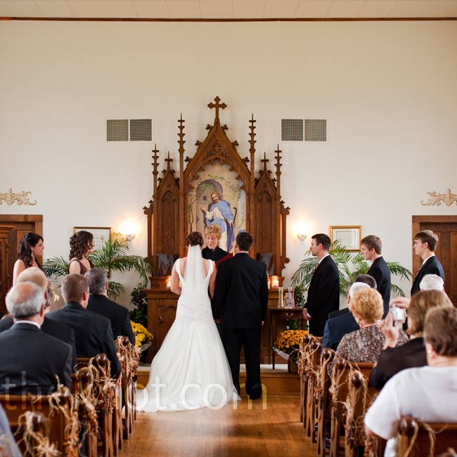Maggie and Zac chose a tiny chapel set on several acres of rolling farmland for the ceremony. Inside, it was simple but filled with beautiful woodwork. Four potted mums at the base of the altar added color and a rustic vibe.