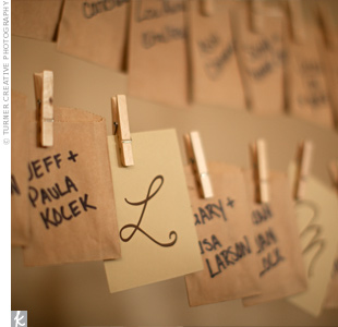 The couple created a giant clothesline-style display for their escort cards. They wrote guests names on mini brown paper bags, which they hung from twine with mini clothespins. Inside each bag, guests found their table assignment.