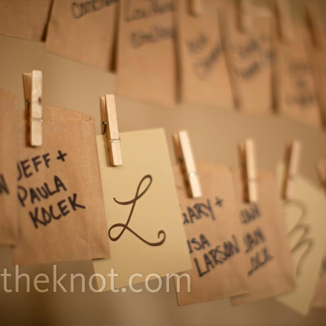 The couple created a giant clothesline-style display for their escort cards. They wrote guests' names on mini brown paper bags, which they hung from twine with mini clothespins. Inside each bag, guests found their table assignment.