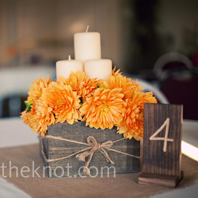 Maggie's dad made wooden boxes for some of the centerpieces. They were filled with either orange dahlias or red carnations and pillar candles of varying heights sat in the center.