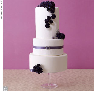 White fondant cake accented with dark purple sugar carnations, lavender ribbon and a rhinestone belt broach accent by Vanilla Bake Shop, VanillaBakeShop.com